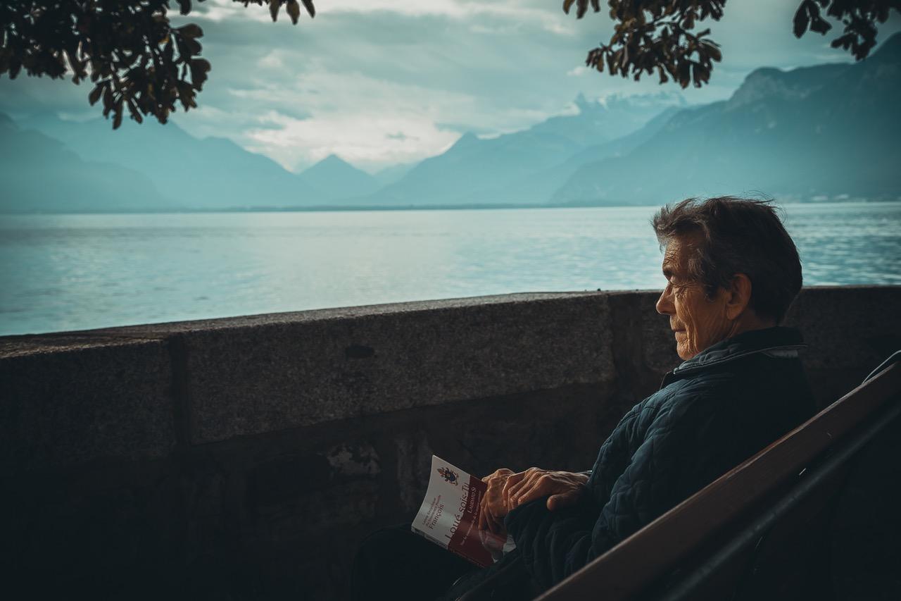 elderly man looking over lake